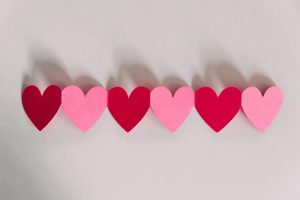 Paper pink and red hearts in a row.