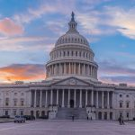 U.S. Capitol building with colorful sunset behind it