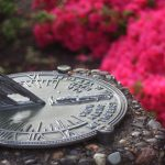 Sundial next to pink flowers