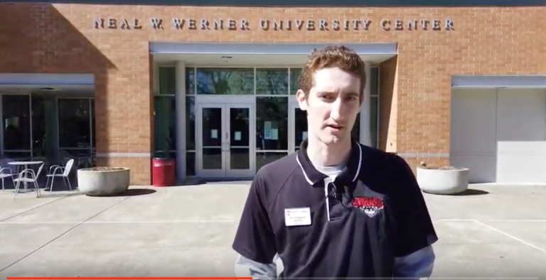 Student standing in front of Werner University Center on a sunny day