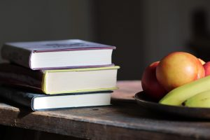 A stack of books next to a plate of fruit