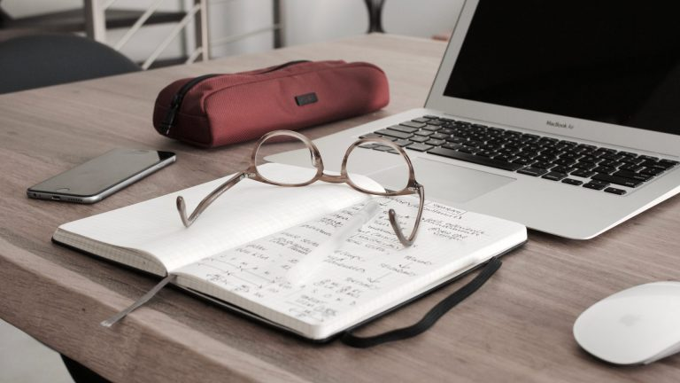 Glasses on a notebook by a computer