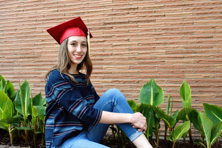 WOU graduate Natalie Legras smiles in front of a brick wall with green plants below. She is wearing a striped shirt, blue jeans, and a WOU graduation cap.