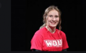 """Camryn Skari smiles for a photograph. Her hair is pulled away from her face, and she is wearing a red shirt with white letters that read """"WOU."""" She is posed in front of a black background"""