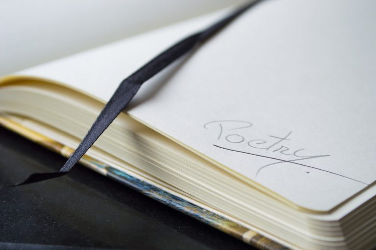 """An open notebook with """"poetry"""" written on the corner of a page"""