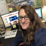 WOU grad April Bradley smiles in front of her computer. She is wearing glasses and a dark blue shirt.