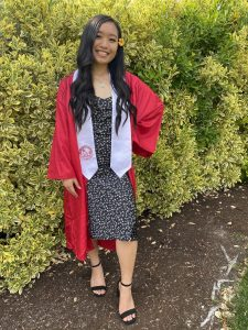 WOU grad Susiele Koga Truong smiles in her red cap and gown. She is wearing a black and white dress underneath, with a white stole around her neck and an orange flower in her hair.