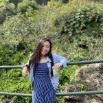 WOU graduate Susiele Koga Truong smiles in front of a railing.She is wearing a blue striped jumpsuit and a light wash denim jacket. She is holding an iced coffee and there is lush greenery behind her.
