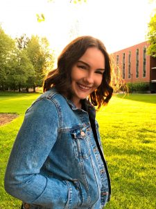 Student is standing on the Ackerman Hall lawn, haloed by the setting sun. She is halfway facing the camera and smiling.