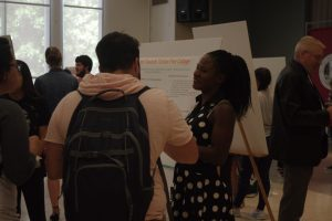 Person standing in front of a poster and talking to a group of people