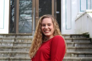 WOU student Megan McAllister smiles in front of an outdoor stairwell. Megan is wearing a bright red shirt.