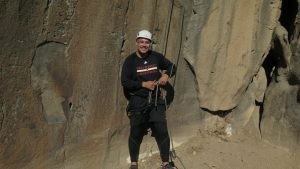 WOU student Jon Montero stands in front of a large rock structure, with rock climbing gear on. John is wearing a black WOU basketball shirt.