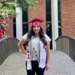 WOU graduate Zoe Chan-Tuyub stands in front of the Natural Science building on campus. She is wearing a white shirt, black pants, a red graduation cap, and a white stole with multiple cords.