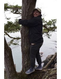 Student stands on a sturdy branch while he hugs a tree. He is wearing hiking gear and smiling at the camera.