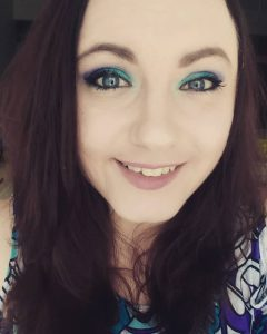 Student wearing bright, glittery eye makeup and smiling straight-on at the camera.