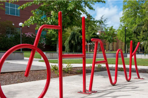 "A red bike rack that spells the name ""Hank"""