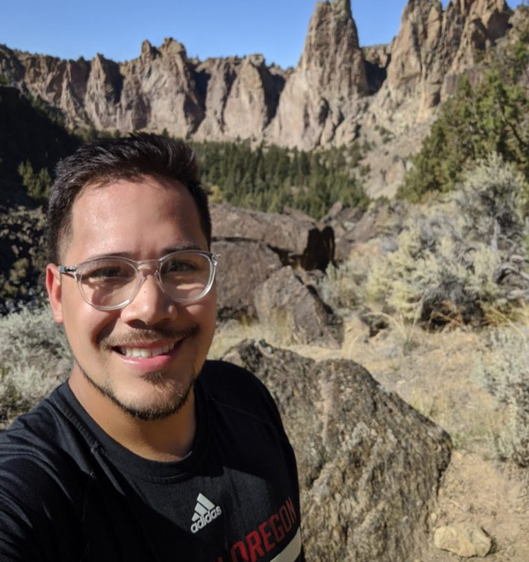 WOU senior Jon Montero is standing in front of large rock structures. Jon is wearing a black Adidas shirt and glasses.