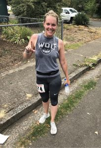 Student dressed in WOU athletic gear, posing for the camera with a smile.
