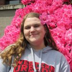 Graduate student Maddie Hannah smiles in front of bright pink flowers, with a pink flower in her hair. She is wearing a light gray WOU sweatshirt.