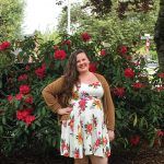 WOU grad Erin Ritchie smiles in front of red flowers. She is wearing a white floral dress and a brown jacket with matching boots.