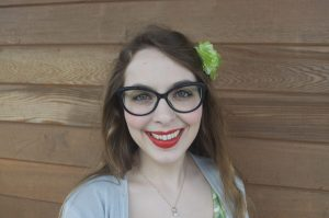 WOU student Heidi Benham smiles in front of a wooden wall. She is wearing a gray shirt, red lipstick, and glasses, and there is a green flower in her hair.