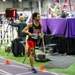 Person running on a track with a WOU uniform on