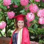 WOU graduate Jennifer Romadka smiles in her red cap and gown in front of bright pink flowers.