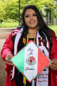 "WOU graduate Gabriela Acevedo-Solis smiles in her graduation cap, stoles, and cords. She is holding her decorated cap in front of her, which reads ""Para mi Familia"" over the Mexican flag."