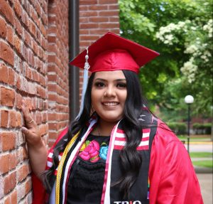 WOU graduate Gabriela Acevedo-Solis poses in her red graduation gown. She is wearing multiple cords and stoles, representing the numerous organizations she has been involved throughout her time at WOU.