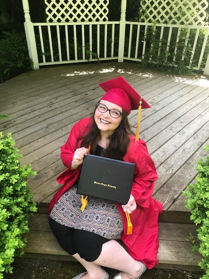 WOU graduate Taylor Dowler smiles in her red graduation cap and gown, and proudly shows off her diploma.