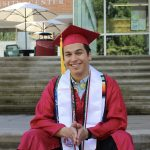 Person sitting in a red graduation cap and gown, smiling