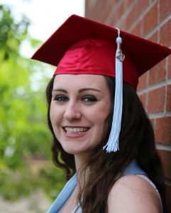 WOU graduate Faith Van Putten smiles in her red graduation cap. She is leaning against a brick wall, and has a white tassel hanging from her cap.