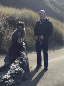 Alumni pictured on the Oregon coast, standing on the sand beside a tall rock, where their dog sits.