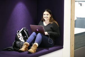 Student sitting in a seating cubby area with a purple background. Student is smiling with laptop on lap