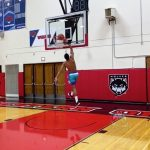 Man in the air dunking a basketball