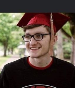 WOU alum Casey Brown smiles in his red graduation cap. He is wearing a black WOU shirt with red lettering, and a tan tassel hangs from his cap, displaying his graduation year (2020)