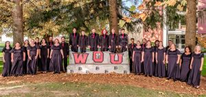 "Western Oregon Chamber Singers pose in front of a large sign that reads ""WOU"" in red font. The 25 members are wearing black dresses or black dress shirts with red ties. They are standing outside, and there are multiple trees with bright green leaves in the background."