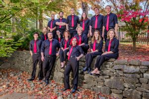 Western Oregon Voices posed outside on a rock wall. The 15 members are all wearing black dress pants, black dress shirts, and red ties.