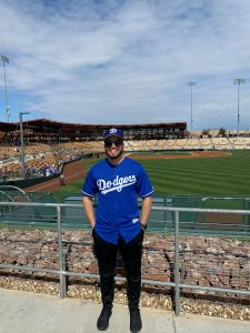 Alumni standing up in the bleachers of a baseball stadium, wearing a Dodgers jersey and smiling.