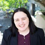 WOU alum Tiffany Blackmon smiles outside. She is wearing a purple shirt with a black blazer.