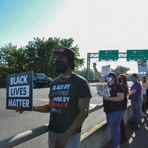 """WOU's Assistant Director of Access and Inclusion Rian Gayle participates in a Black Lives Matter protest in Salem, Oregon. Gayle is wearing a shirt that reads """"BLACK BY NATURE, PROUD BY CHOICE."""" He is also wearing a black face covering, a black and red hat, and is holding a sign that reads """"Black Lives Matter."""" Other protesters are behind him holding similar signs."""