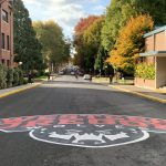Painted WOU logo on a street with brick buildings and trees in fall in the background