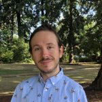 Assistant Professor of Psychological Science Jay Schwartz smiles for a photograph. He is wearing a white printed shirt and is standing in the woods.
