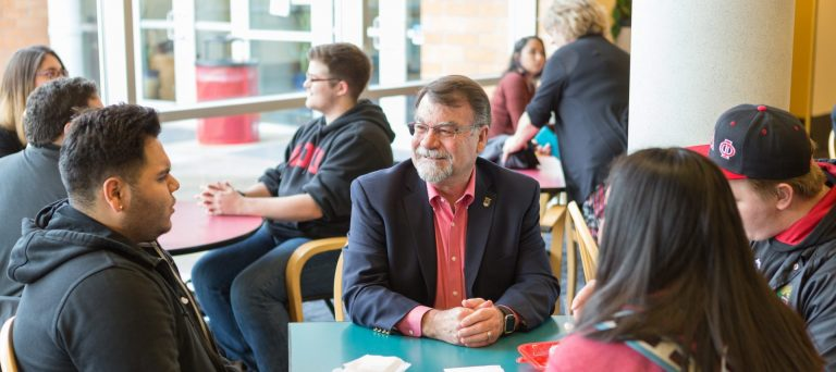 President Rex Fuller sitting at a table with WOU students with more WOU students sitting at tables behind him