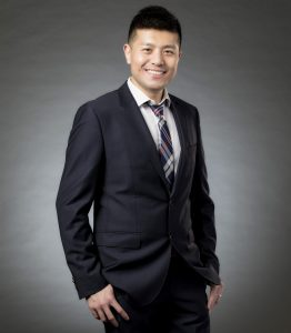 Wu poses in front of a gray background, smiling and wearing a black suit.