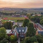 Aerial view of Western Oregon University campus with the tops of several brick buildings, lots of trees, a track, and rolling hills in the background