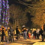 Multiple people gather around the Giant Sequoia Tree in front of Campbell Hall, lit up with holiday lights.