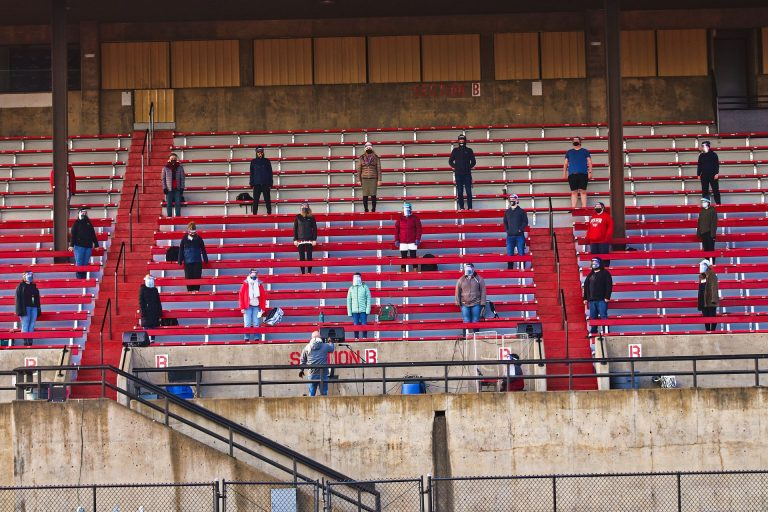 WOU Concert Choir performs in McArthur Field stadium. Approximately 20 students are spread out along the red bleachers, wearing masks and face shields.