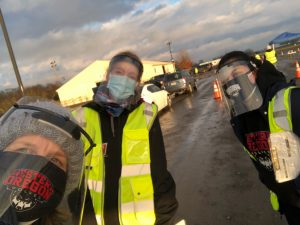 Three WOU people wearing masks, shields and safety vests at a COVID-19 testing event