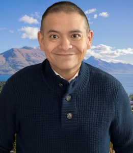 WOU professor Lucas Cordova stands in front of a mountain and greenery background. He is wearing a navy blue button-up sweater.